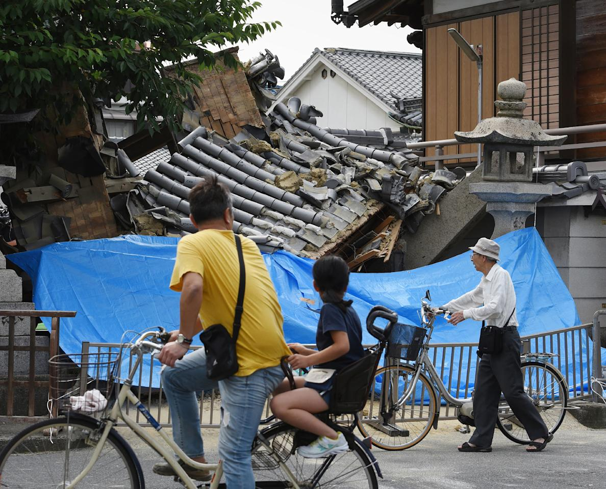 <p>People pause to look at a collapsed house following an earthquake in Ibaraki City, north of Osaka prefecture on June 18, 2018. (Photo: STR/AFP/Getty Images) </p>