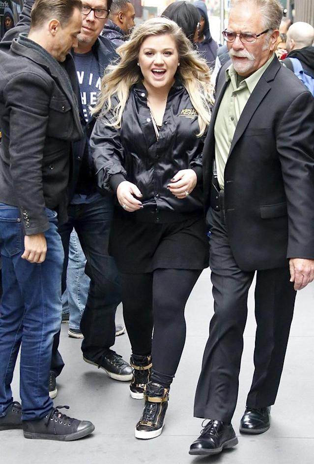 "<p>The ""Love So Soft"" crooner was all smiles while outside the SiriusXM radio station in NYC. Clarkson looked very rock 'n' roll in an all black outfit topped off with a black satin jacket that had ""Kelly"" stitched on the front. (Photo: Best Image/BACKGRID) </p>"