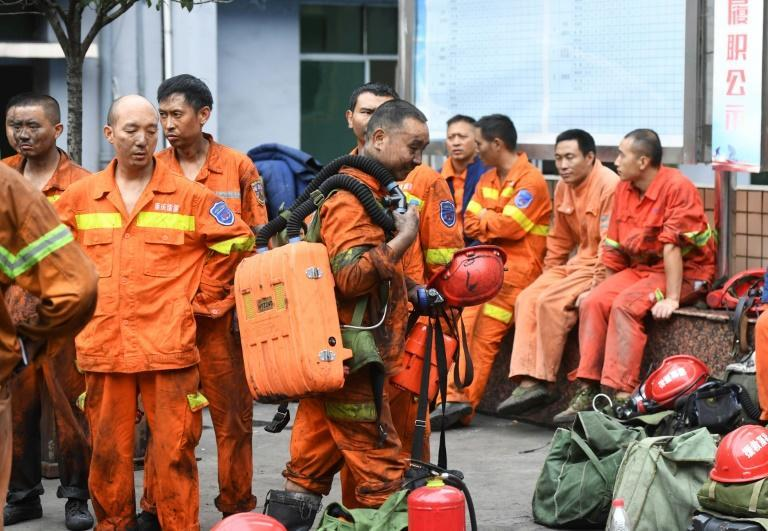 Exhausted rescue workers outside the Songzao mine near Chongqing