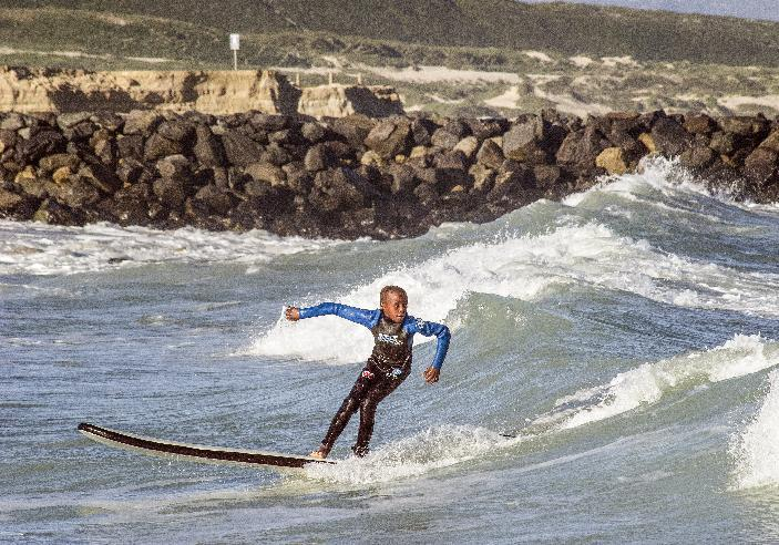 A boy taking part in the Waves for Change programme surfs at Monwabisi Beach, Khayelitsha, on August 7, 2014 (AFP Photo/Rodger Bosch)