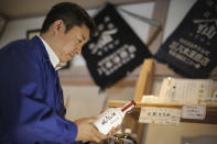 """FILE - In this March 5, 2015, file photo, Michihiro Kono, president of Yagisawa Shoten Co., holds his company's soy sauce bottle, named """"the miracle,"""" at his company's new headquarters in Rikuzentakata, Iwate Prefecture, northeastern Japan. Just a month after a tsunami smashed into the city of Rikuzentakata, soy sauce maker Kono inherited his family's two-century-old business from his father. (AP Photo/Eugene Hoshiko, File)"""