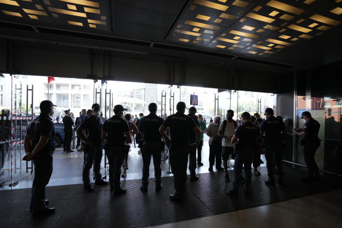 Police officers check passenger's documents at the entrance of Porta Garibaldi train station, in Milan, Italy, Wednesday, Sept. 2, 2021. Italy's government vowed to crack down on demonstrators threatening to block train tracks throughout the country Wednesday as a rule requiring COVID-19 tests or vaccines to use public transportation for long-distance domestic travel took effect. (AP Photo/Luca Bruno)
