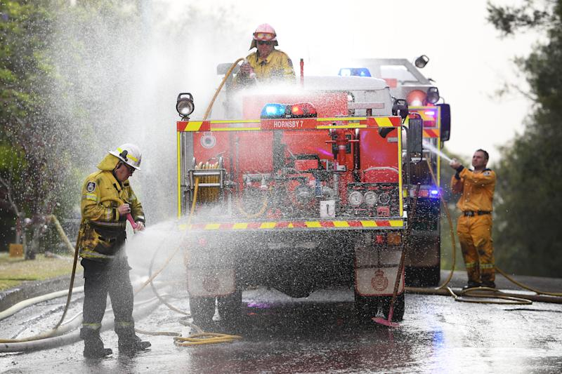 NSW Rural Fire Service crews wash chemical fire retardant off their truck after it was dropped to protect houses on Canoon Rd and Barwon Avenue, South Turramurra, north of Sydney.
