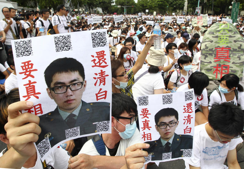 "In this image taken on July 20, 2013, in Taipei, Taiwan, protesters hold posters that read ""Give the truth"" next to portraits of Taiwan soldier Hung Chung-chiu who died in early July after being forced to perform a vigorous regime of calisthenics in sweltering heat on a base in suburban Taipei. The death of the 24-year-old soldier has set off a wave of anger on the democratic island of 23 million people, further undermining the already unpopular administration of President Ma Ying-jeou, and raising hard questions about the future of the island's military. (AP Photo) TAIWAN OUT"