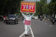 """A man wearing protective gear holds a sign reading """"Celebrate New Year's Eve 2021 at home"""" and """"adhere to health protocols"""" at the Solo, Central Java Province"""