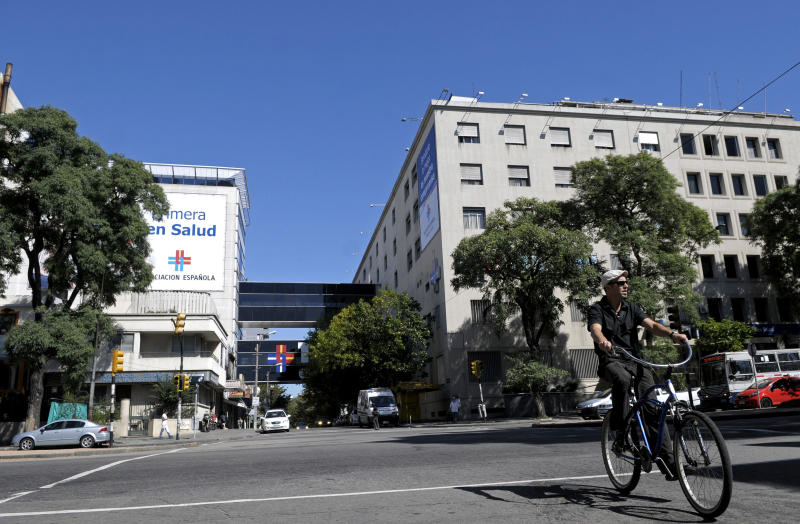 A man rides his bike near the private health institution Asociacion Espanola, or Spanish Association, in Montevideo, Uruguay, Sunday March 18, 2012. Uruguayan police say an investigation into dozens of possibly induced deaths at two hospitals, including Asociacion Espanola, has led to the detention of at least two people. Police inspector Jose Luis Roldan said Sunday that officials suspect that hospital workers brought a sort of poison from Brazil and gave it to patients who were in critical condition. (AP Photo/Matilde Campodonico)