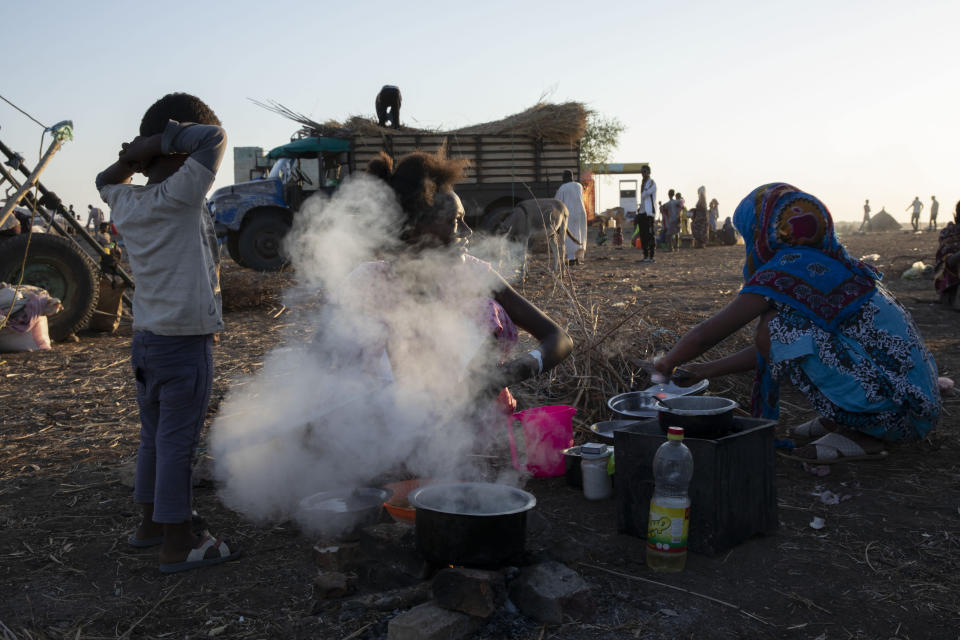 Tigray refugees who fled the conflict in the Ethiopia's Tigray prepare breakfast for their families at Hamdeyat Transition Center near the Sudan-Ethiopia border, eastern Sudan, Thursday, Dec. 3, 2020. Ethiopian forces on Thursday blocked people from the country's embattled Tigray region from crossing into Sudan at the busiest crossing point for refugees, Sudanese forces said.(AP Photo/Nariman El-Mofty)