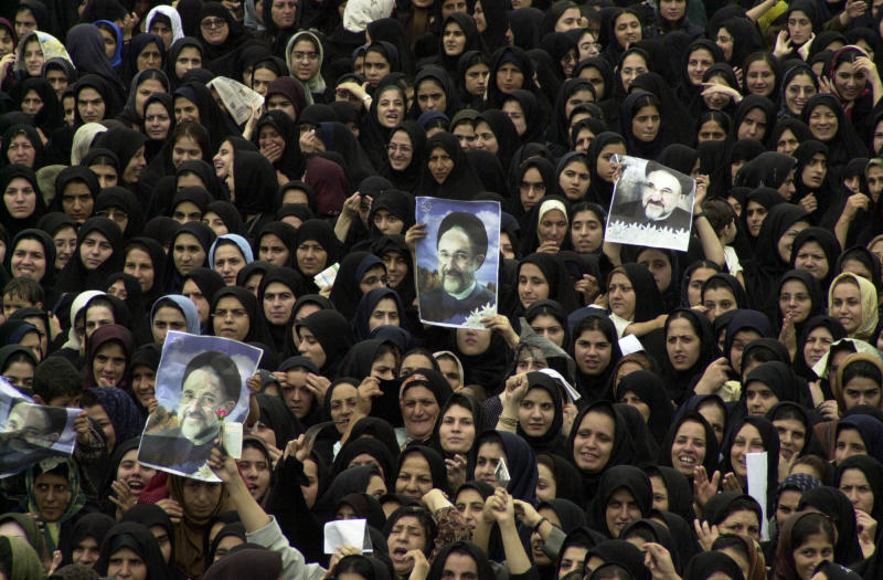 FILE - In this Monday, Sept. 30, 2002 file photo, Iranian women hold pictures of President Mohammad Khatami during a public welcoming ceremony at the Azadi stadium in the city of Rasht northwest of capital Tehran, Iran. Many reformists are expected to sit out the June 14 voting in a silent protest over the crackdowns that have left them leaderless and demoralized. Others unwilling to boycott the election are rallying around a last-ditch call for help to Khatami, who is seen increasingly as their only credible hope at the ballot box.(AP Photo/Vahid Salemi, File)