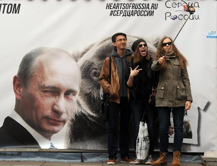 People pose for a selfie photograph in front of a banner depicting Russian President Vladimir Putin in St. Petersburg on May 2, 2015 (AFP Photo/Olga Maltseva)