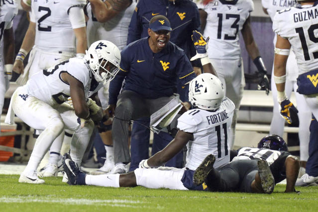 West Virginia safety Tykee Smith (23) and cornerback Nicktroy Fortune (11) celebrate the broken up pass to TCU wide receiver Al'Dontre Davis (80) that turned the ball over to West Virginia in the final minute in an NCAA college football game Friday, Nov. 29, 2019, in Fort Worth, Texas. (AP Photo/Richard W. Rodriguez)