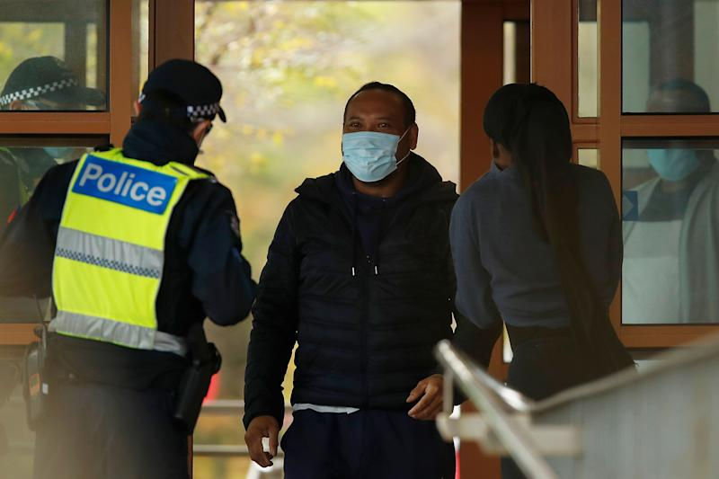 MELBOURNE, AUSTRALIA - JULY 07: People speak with police at the entrance to one of the public housing towers in Kensington on July 07, 2020 in Melbourne, Australia.  (Photo: Daniel Pockett via Getty Images)
