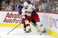 Carolina Hurricanes' Dougie Hamilton (19) plays the puck in front of Columbus Blue Jackets' Boone Jenner (38) during the first period of an NHL hockey game in Raleigh, N.C., Saturday, Oct. 12, 2019. (AP Photo/Karl B DeBlaker)
