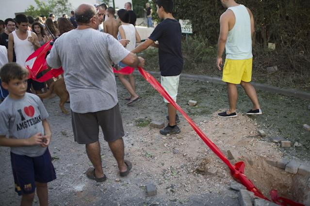 """GESHER-HAZIV, ISRAEL - AUGUST 22: People look at the damage believed to have been caused by the fallout of an """"Iron Dome"""" interceptor rocket after intercepting one of four rockets fired at Israel from Lebanon on August 22, 2013 in Kibbutz Gesher Haziv, Israel. According to an Israeli military spokesman, four rockets were fired toward northern Israel from southern Lebanon but none landed in Israel's territory. No-one was reported to have been injured but some light damage to a street and vehicle was believed to have been caused by the debris from Israel's rocket defence system. (Photo by Ilia Yefimovich/Getty Images)"""
