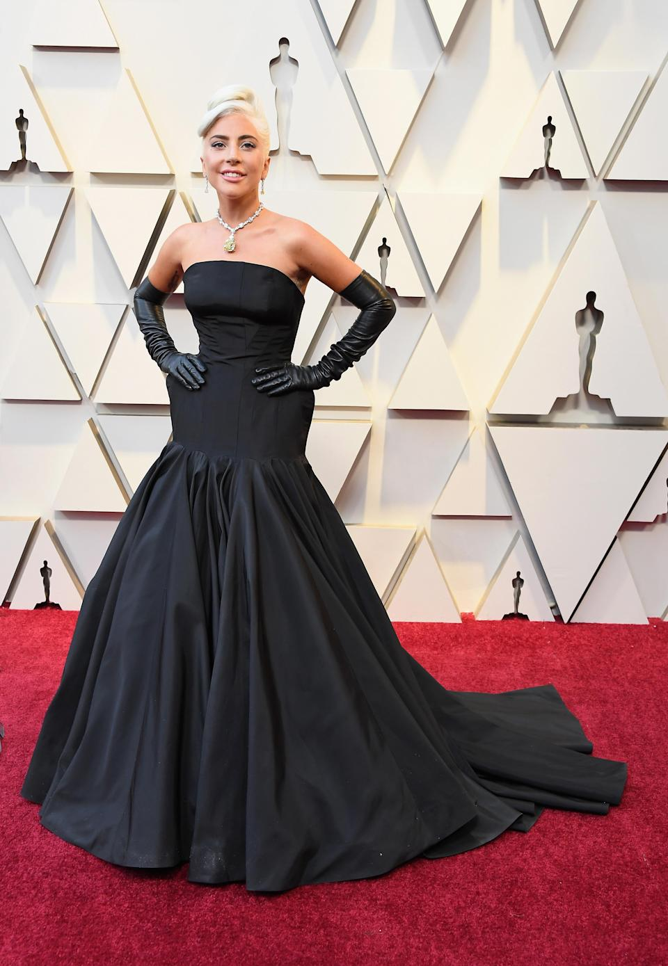 """<p>Lady Gaga capped-off awards season with her most glamorous look yet. The """"A Star is Born"""" actress wore a strapless gown with a structured hip detail by Alexander McQueen. The best actress nominee added extra glamour to her look by wearing a 128 carat cushion cut diamond necklace worth a reported $50 million from Tiffany & Co. The showstopping piece was last worn by Audrey Hepburn in the iconic film, """"Breakfast at Tiffany's."""" <em>[Photo: Getty]</em> </p>"""