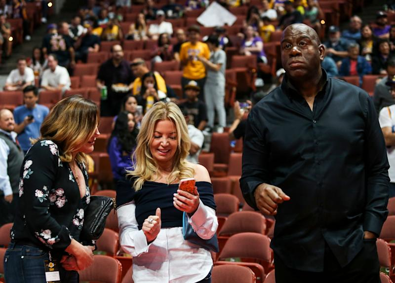 Jeanie Buss, center, and Magic Johnson attend an NBA preseason basketball game between Los Angeles Lakers and Minnesota Timberwolves in Anaheim, Calif., Saturday, Sept. 30, 2017. (AP Photo/Ringo H.W. Chiu)