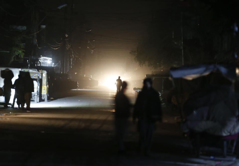 People are silhouetted on vehicle's headlights on a dark street during widespread power outages in Rawalpindi, Pakistan, Sunday, Jan. 10, 2021. Pakistan's national power grid experienced a major breakdown late night on Saturday, leaving millions of people in darkness, local media reported. (AP Photo/Anjum Naveed)