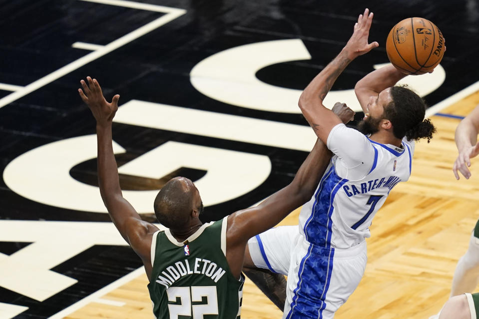 Milwaukee Bucks forward Khris Middleton (22) tries to stop Orlando Magic guard Michael Carter-Williams (7) as he takes a shot during the second half of an NBA basketball game, Sunday, April 11, 2021, in Orlando, Fla. (AP Photo/John Raoux)