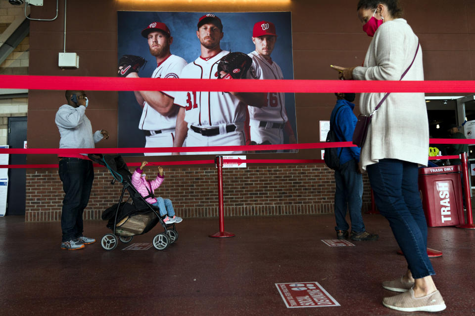 Early voting begins in the District of Columbia as voters wait in line at an early voting center at Nationals Park, Tuesday, Oct. 27, 2020, in Washington. (AP Photo/Jacquelyn Martin)