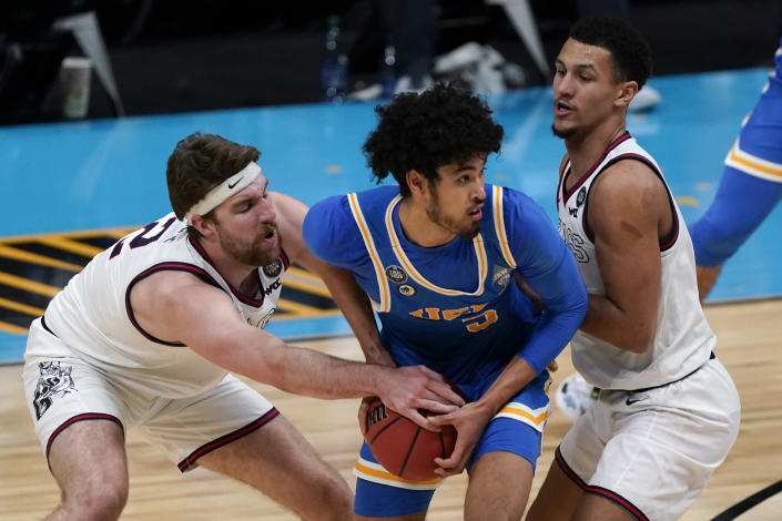 UCLA guard Johnny Juzang, center, looks to pass between Gonzaga forward Drew Timme, left, and guard Jalen Suggs, right, during the second half of a men's Final Four NCAA college basketball tournament semifinal game, Saturday, April 3, 2021, at Lucas Oil Stadium in Indianapolis. (AP Photo/Michael Conroy)