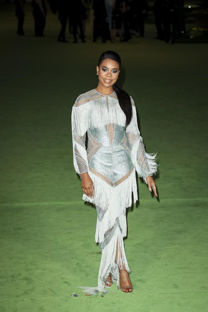 A woman in a silver, fringe dress posing on a green carpet