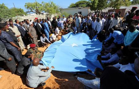 Relatives and government officials bury the dead body of Somalia's public works minister Abbas Abdullahi Sheikh Siraji who was shot and killed in the capital Mogadishu