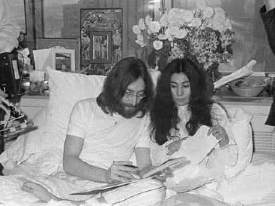 John Lennon and Yoko Ono are flanked by journalists in Room 1742 of the Queen Elizabeth Hotel in Montreal in 1969. The couple spent two weeks in the hotel room in bed in a performance art protest to promote peace during the Vietnam War. This collaboration between the couple and others are part of a survey exhibition of Ono's works opening at the Vancouver Art Gallery on Oct. 9. (Jacques Bourdon/Le Journal de Montreal/Montreal Museum of Fine Arts - image credit)