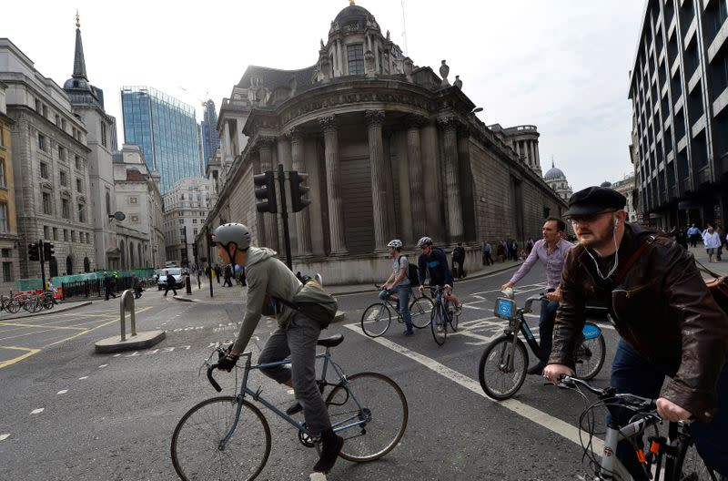FILE PHOTO: Commuters cycle past the Bank of England in the City of London