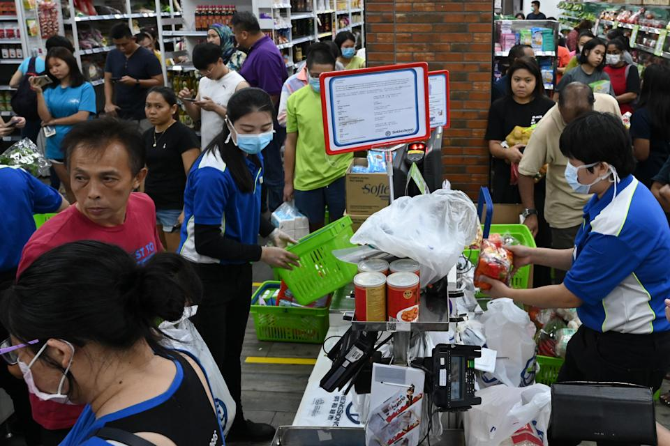 People queue to pay for groceries at a supermarket here on 3 April, 2020. (PHOTO: AFP via Getty Images)