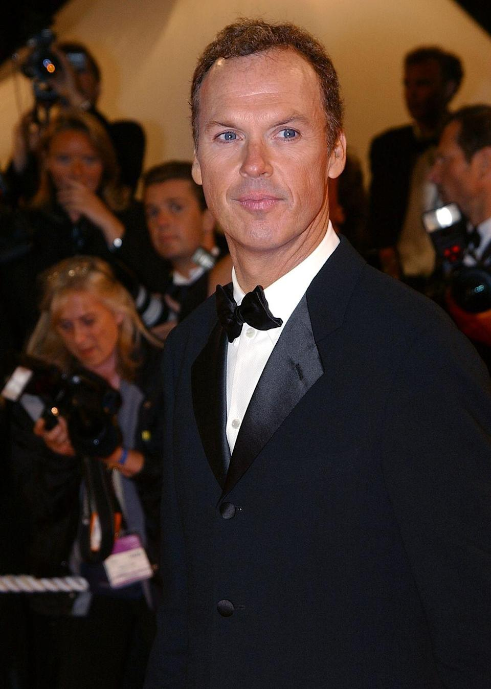 <p>Michael Keaton flashed a smile as he arrived on the red carpet of the Cannes Film Festival, sporting his signature short brown hair in 2002. </p>