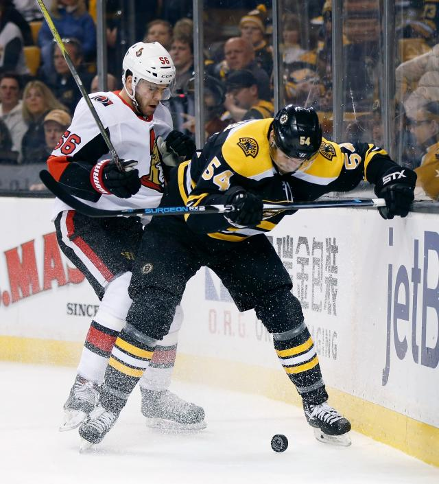 Ottawa Senators' Magnus Paajarvi (56), of Sweden, and Boston Bruins' Adam McQuaid (54) battle for the puck during the first period of an NHL hockey game in Boston, Saturday, April 7, 2018. (AP Photo/Michael Dwyer)