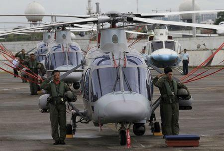 FILE PHOTO: Philippine Air Force pilots stand next to newly acquired AgustaWestland AW109E helicopters during a ceremony at the Villamor Air Base in Pasay city, metro Manila
