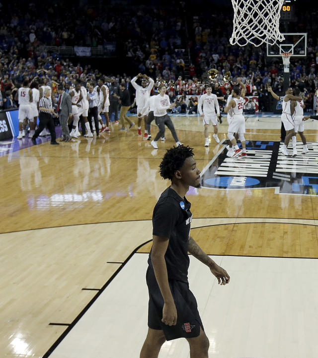 San Diego State guard Jeremy Hemsley walks off the court while Houston players celebrate in the background after their NCAA men's college basketball tournament first-round game Thursday, March 15, 2018, in Wichita, Kan. Houston won 67-65. (AP Photo/Charlie Riedel)