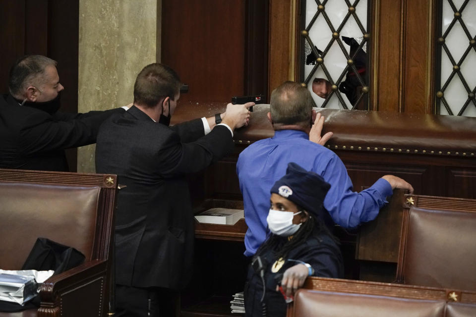 Police with guns drawn watch as protesters try to break into the House Chamber at the U.S. Capitol on Wednesday, Jan. 6, 2021, in Washington. (J. Scott Applewhite/AP)