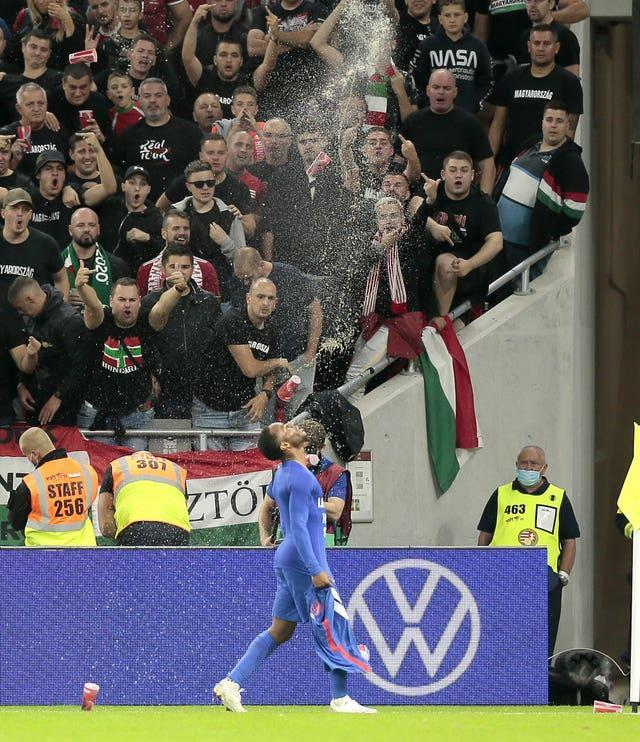 Hungary fans gesture and throw cups as Raheem Sterling celebrates his goal