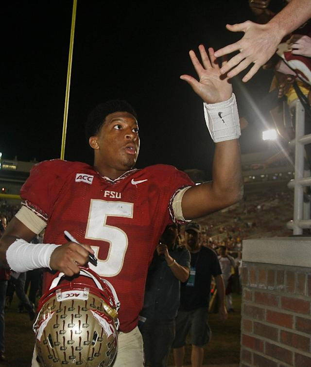 Florida State quarterback Jameis Winston (5) high-fives with fans after an NCAA college football game against Idaho on Saturday, Nov. 23, 2013 in Tallahassee, Fla. Florida State beat Idaho 80-14. (AP Photo/Phil Sears)