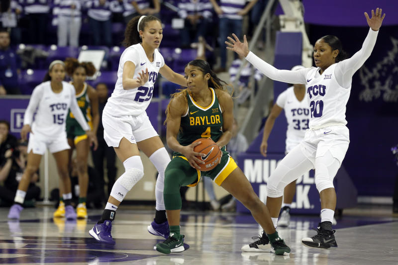 Baylor guard Te'a Cooper, center, is doubled by TCU guard Kianna Ray, left, and guard Lauren Heard, right, during the second half of an NCAA college basketball game in Fort Worth, Texas, Wednesday, Jan. 22, 2020. Baylor won 66-57. (AP Photo/Ray Carlin)