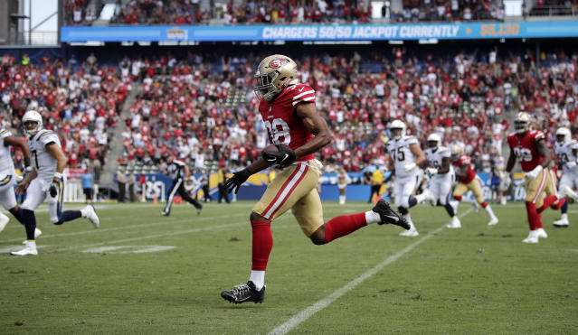 San Francisco defensive back Antone Exum runs back an interception during a Chargers home game, but note all the 49ers' red in the crowd. (AP)
