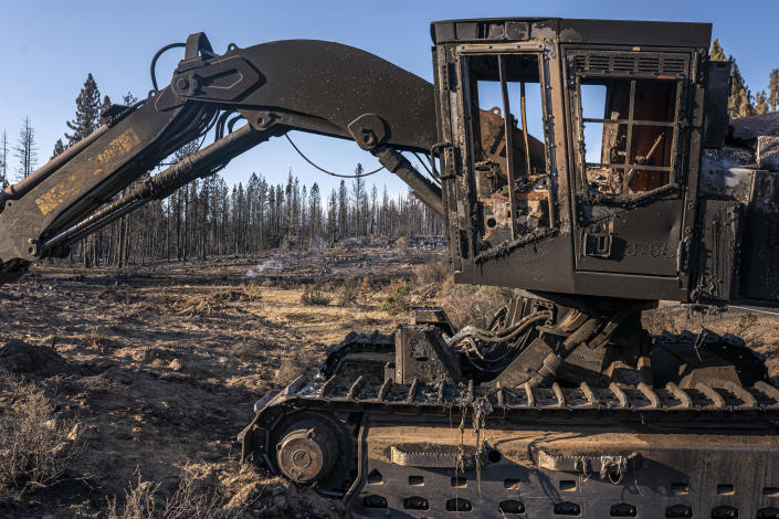 A damaged and abandoned excavator is seen in an area burned by the Bootleg Fire on Wednesday, July 21, 2021 in Bly, Ore. (AP Photo/Nathan Howard)