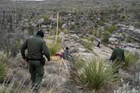 Border patrol agents Arain Carrera and Thaddeus Cleveland approach an injured Guatemalan migrant in a remote canyon of west Texas (AFP Photo/Paul Ratje)