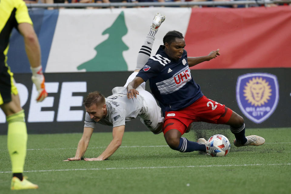 New England Revolution defender Jon Bell (23) clears the ball from the box ahead of CF Montreal midfielder Djordje Mihailovic (8) during the first half of an MLS soccer match, Sunday, July 25, 2021, in Foxborough, Mass. (AP Photo/Mary Schwalm)