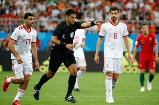 Paraguayan referee Enrique Caceres points to the penalty spot during Portugal's game against Iran
