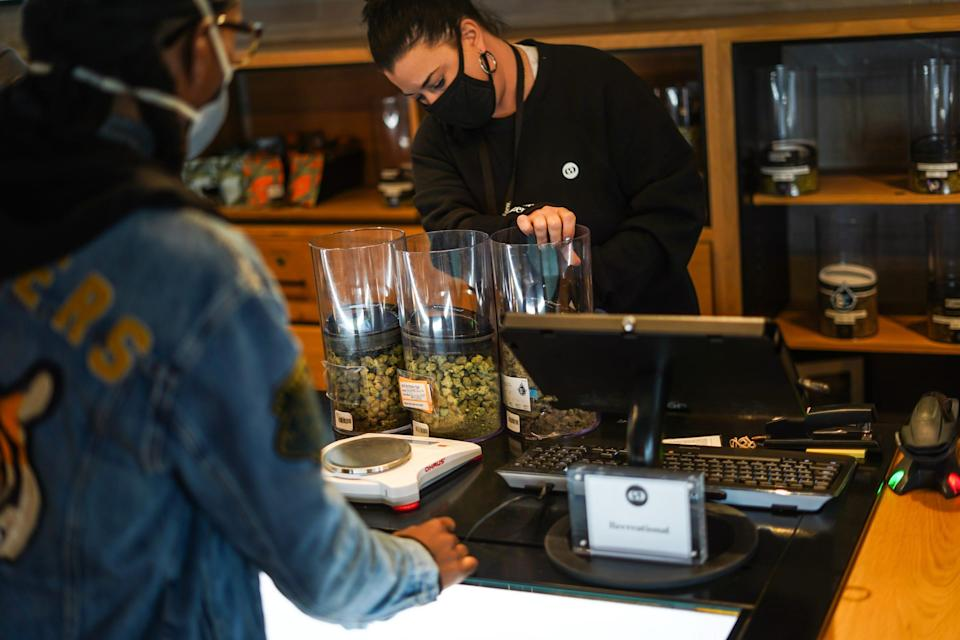 Common Citizen dispensary adviser DeeAnn Edgley helps fill an order at Common Citizen dispensary in Flint, Mich., on April 22. The business sells medical and recreational marijuana products.
