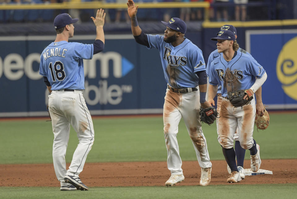 Tampa Bay Rays' Joey Wendle (18), Manuel Margot, center, and Taylor Walls line up after a win over the Baltimore Orioles during a baseball game Sunday, June 13, 2021, in St. Petersburg, Fla. (AP Photo/Steve Nesius)