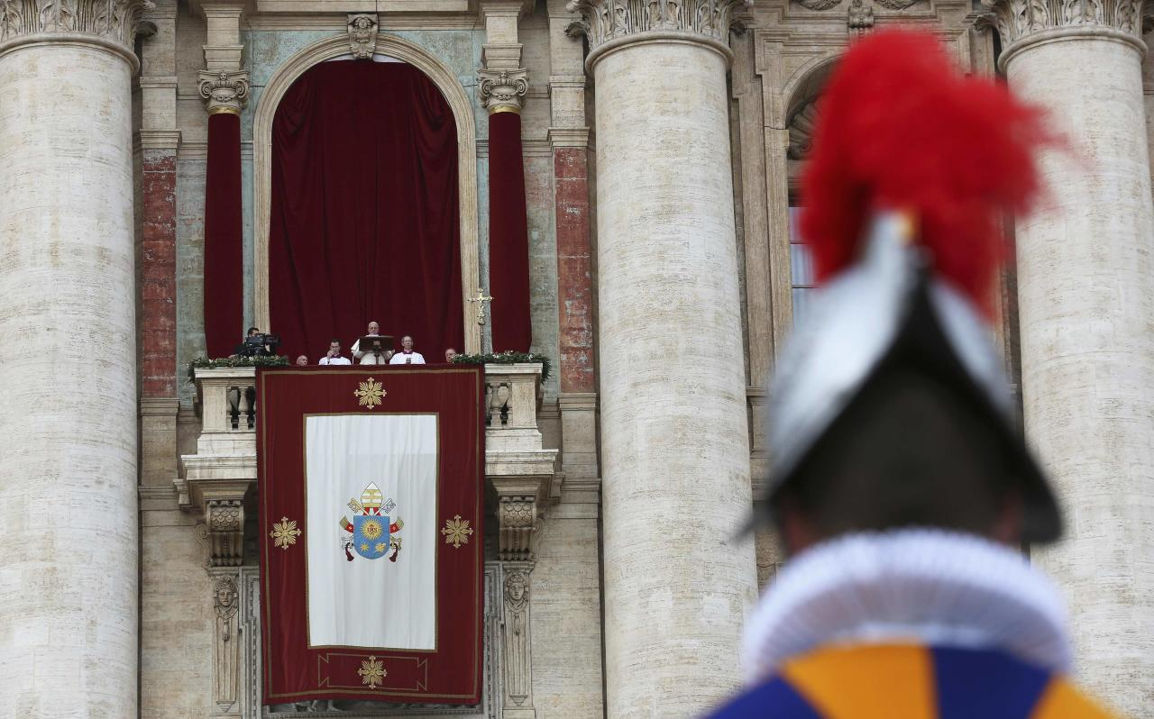 """A Swiss Guard stands as Pope Francis delivers his first """"Urbi et Orbi"""" (to the city and world) message from the balcony overlooking St. Peter's Square at the Vatican December 25, 2013. Francis, celebrating his first Christmas as Roman Catholic leader, on Wednesday called for dialogue to end the conflict in South Sudan and all wars, saying everyone should strive to be personal peacemakers. REUTERS/Alessandro Bianchi (VATICAN - Tags: RELIGION TPX IMAGES OF THE DAY POLITICS)"""