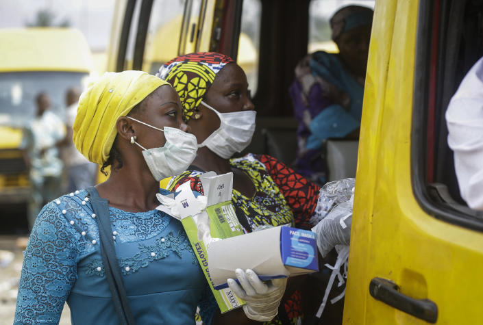 Women sell face masks and gloves, to prevent the spread of the new coronavirus, to passengers at a public minibus station in Lagos, Nigeria Friday, March 27, 2020. The new coronavirus causes mild or moderate symptoms for most people, but for some, especially older adults and people with existing health problems, it can cause more severe illness or death. (AP Photo/Sunday Alamba)