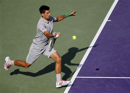 Mar 26, 2014; Miami, FL, USA; Novak Djokovic hits a forehand against Andy Murray (not pictured) on day ten of the Sony Open at Crandon Tennis Center. Geoff Burke-USA TODAY Sports