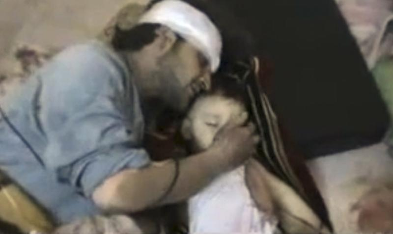 This Saturday, Feb. 18, 2012 image taken from amateur video made available by the Shaam News Network Wednesday Feb. 22, 2012, shows a man touching the face of his son, who was purportedly killed by Syrian government shelling in Homs Syria. (AP Photo/Shaam News Network) THE ASSOCIATED PRESS CANNOT INDEPENDENTLY VERIFY THE CONTENT, DATE, LOCATION OR AUTHENTICITY OF THIS MATERIAL.