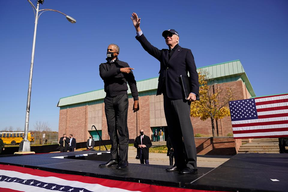 Former Vice President Joe Biden, right, and former President Barack Obama greet each other at a rally at Northwestern High School in Flint, Mich., on Oct. 31, 2020.