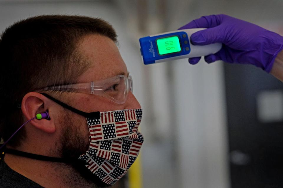 Kyle Pearson has his temperature checked at the start of his shift at Vibram Corporation in North Brookfield, MA.