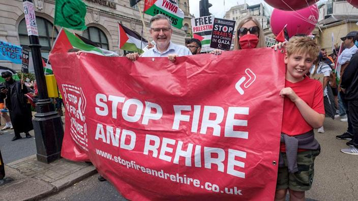 """Protesters carry a banner saying """"stop fire and rehire"""""""
